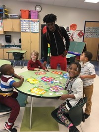 students playing a number matching game with a Learning Center student teacher