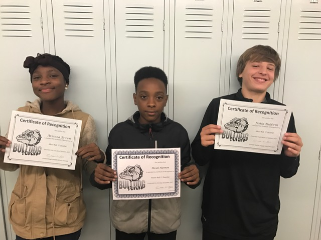 three students with their Honor Roll and Merit Roll certificates
