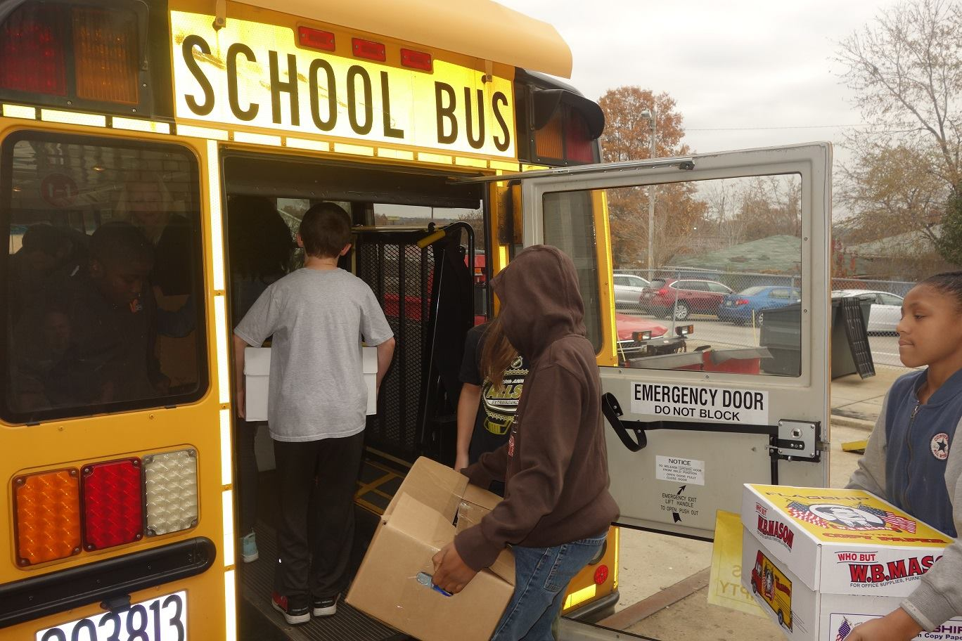 students loading boxes of canned goods onto a school bus