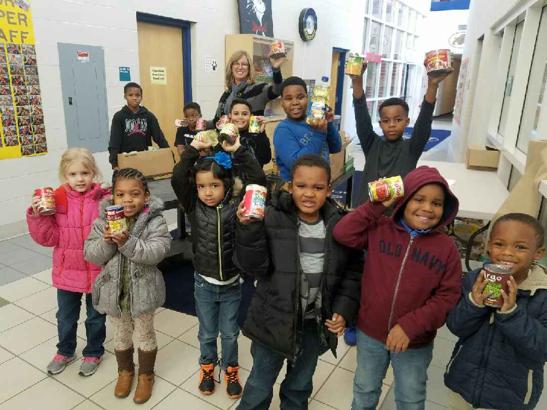 students holding canned goods and boxes of canned goods