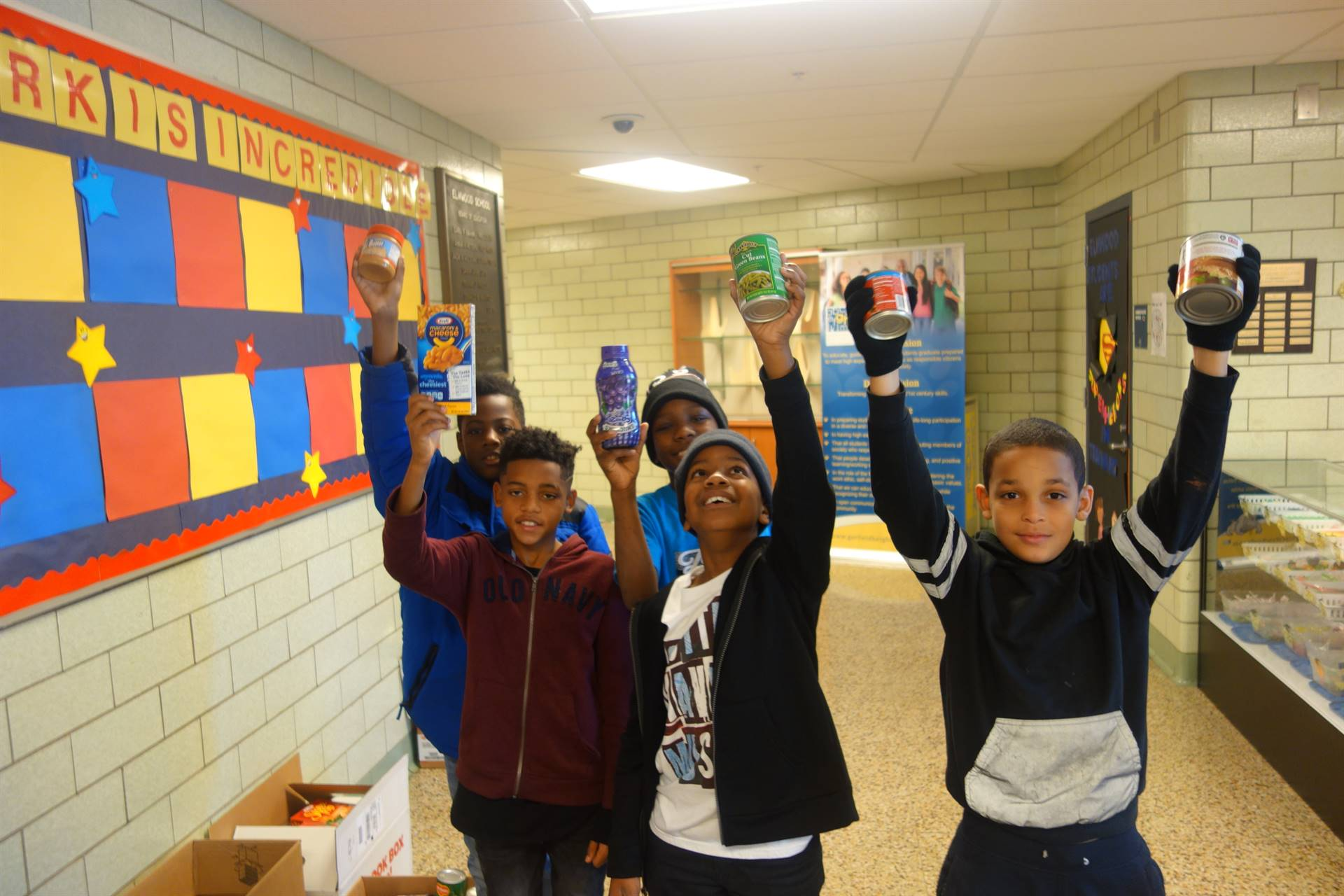 students posing with canned goods