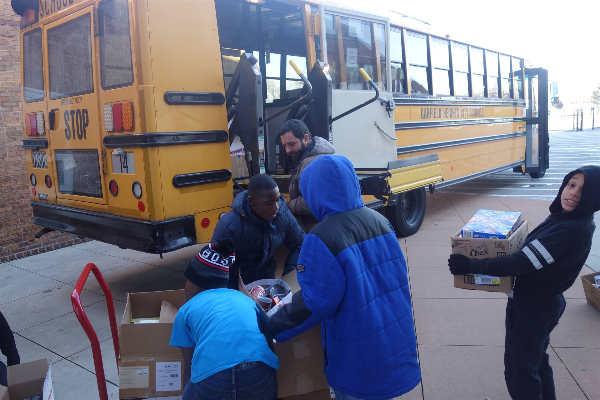 students and staff loading boxes onto a school bus