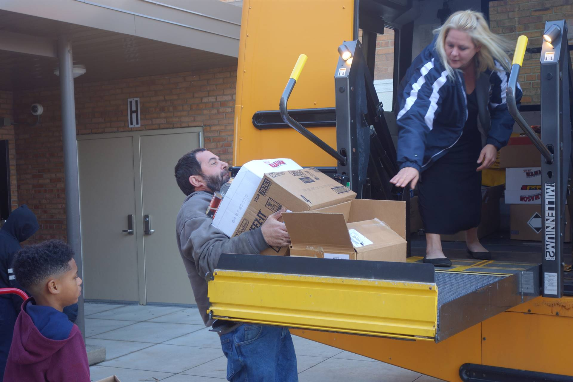 staff loading boxes onto a school bus lift