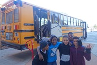 students posing in front of a school bus
