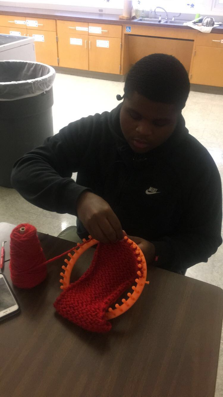 student using a circle loom to make a scarf