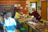 K-Club students getting pizza from Mrs. Abraham