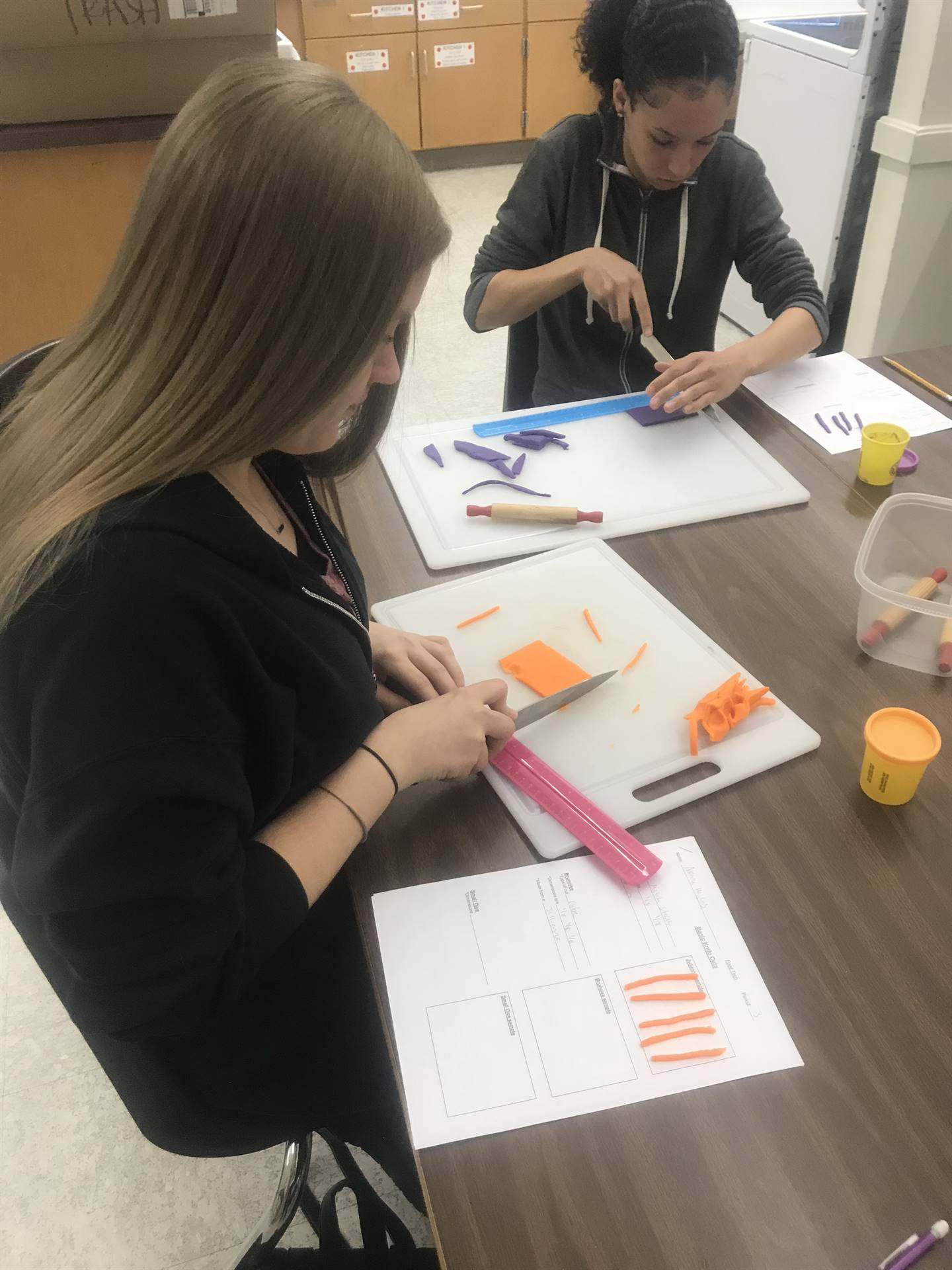 students cutting play dough with knives