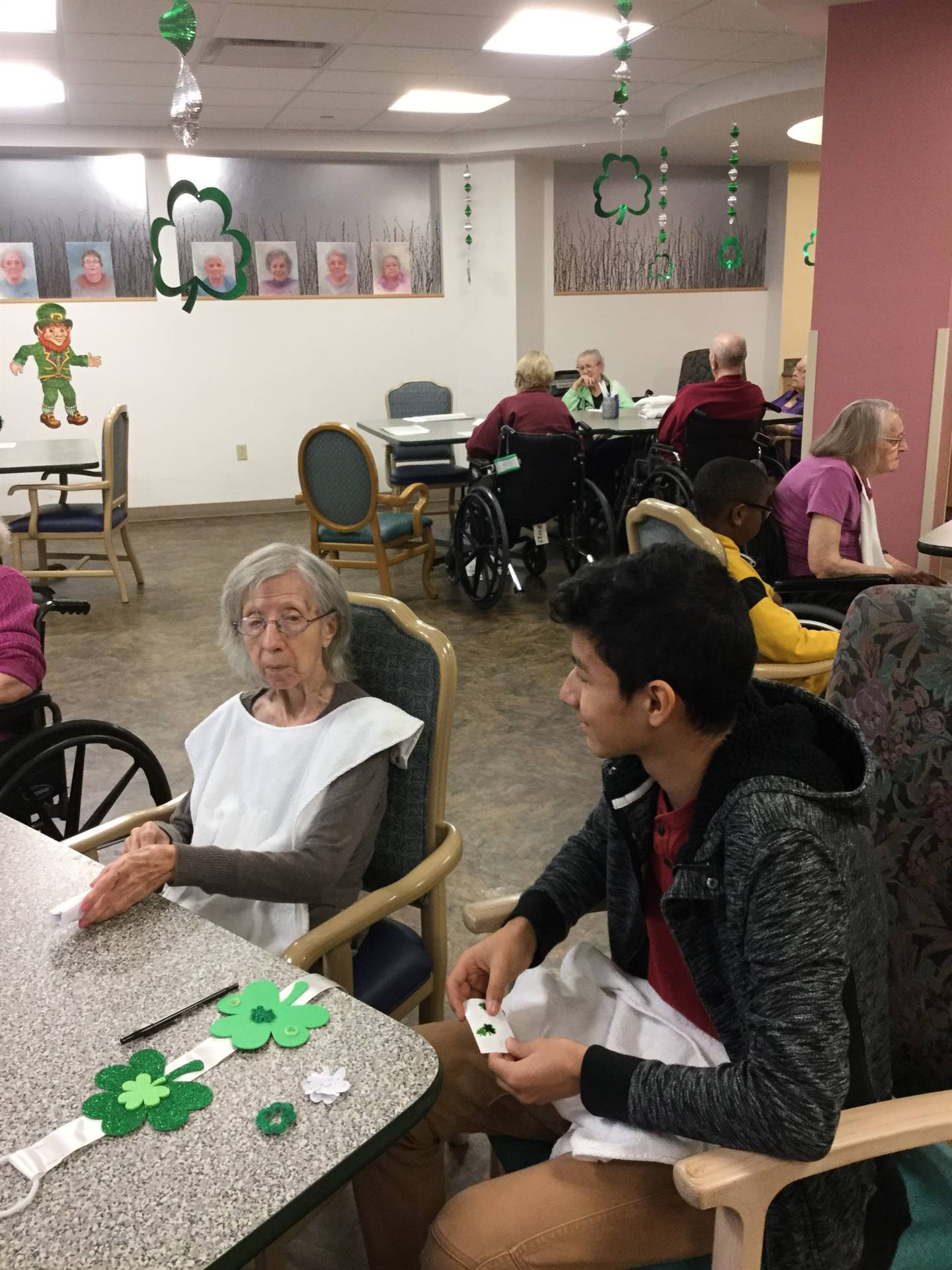 students with residents at Jennings Hall making St. Patrick's Day crafts