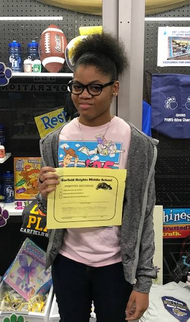Student holding her PBIS award certificate.