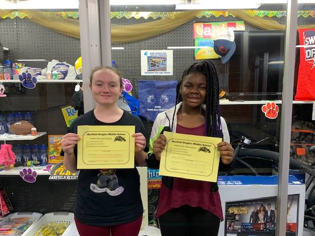 Two girls holding their PBIS Certificates.