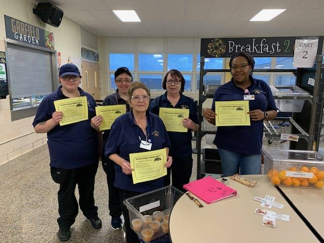 Cafeteria staff with their positive referral certificates.
