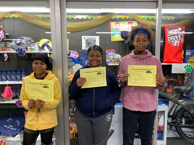 Students holding their Positive Behavior Referrals.